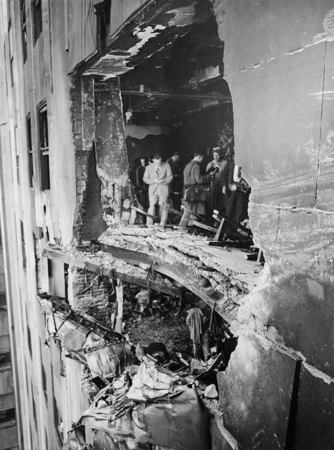 Specialistai apžiūri skylę, kuri liko po bombonešio smūgio.