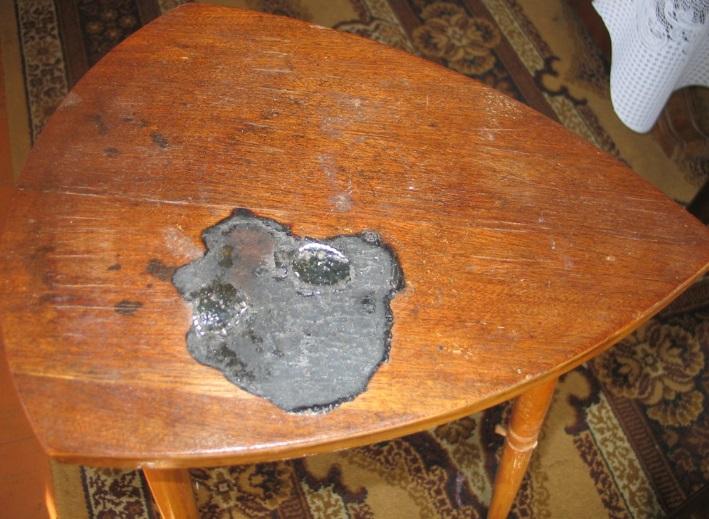 Stalelis su žymėmis sudegintų mobiliųjų telefonų